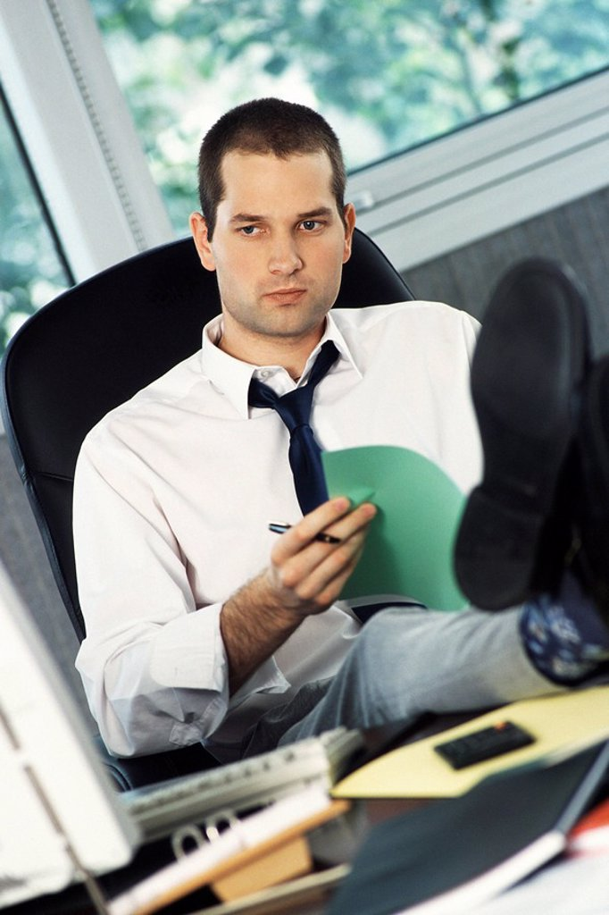 Stock Photo: 1569R-9055527 Man with feet up on office desk holding document, looking away