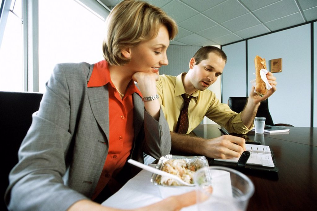 Business associates discussing calendar event over casual lunch in conference room : Stock Photo