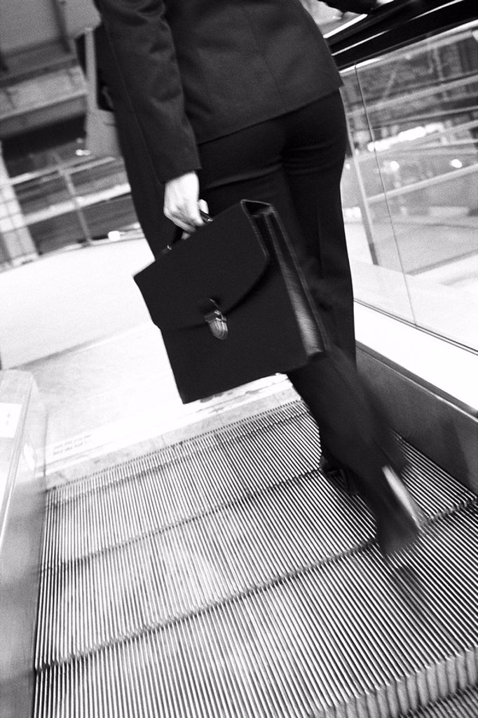 Businesswoman ascending escalator, rear view : Stock Photo