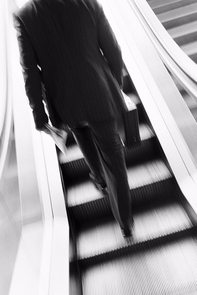 Businessman ascending escalator, rear view : Stock Photo