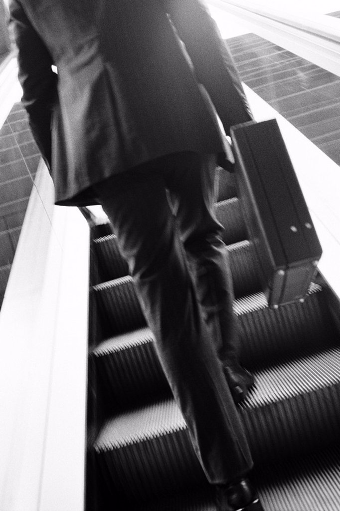 Businessman carrying briefcase ascending escalator, rear view : Stock Photo