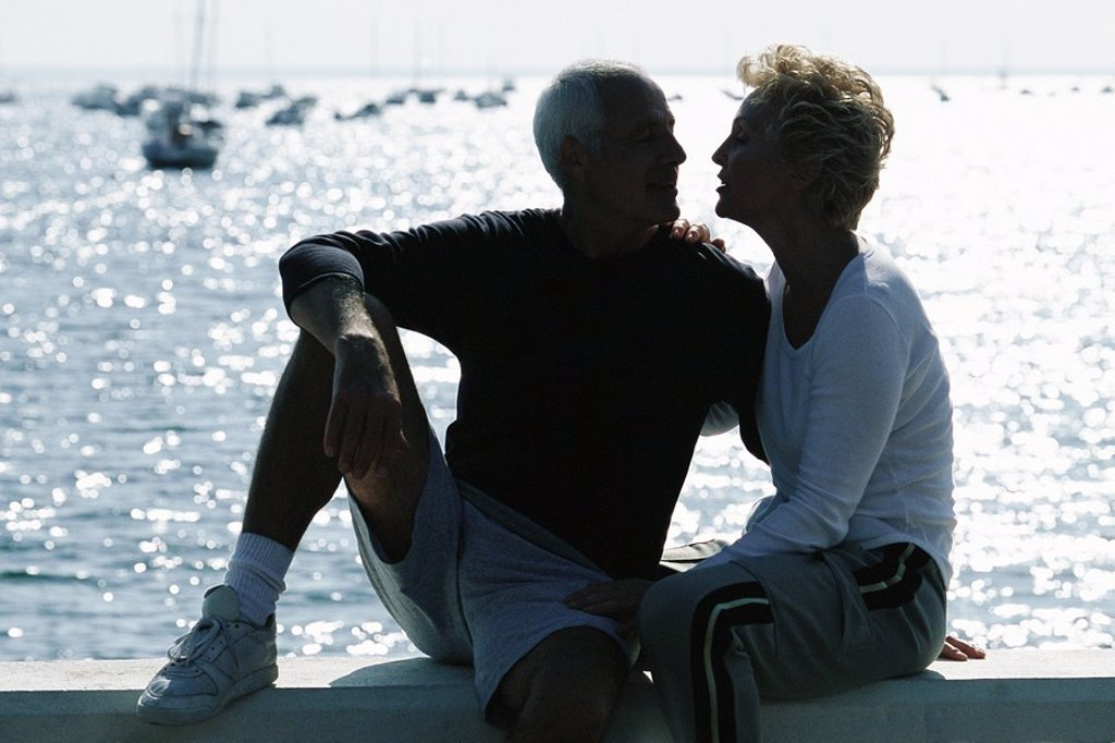 Stock Photo: 1569R-9055567 Mature couple sitting together on pier, backlit