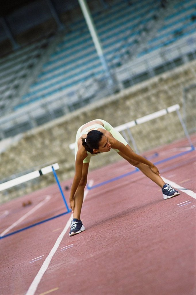 Woman doing stretches on running track : Stock Photo