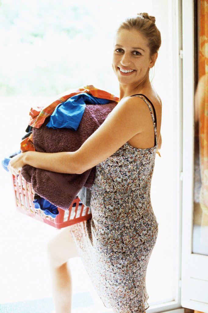 Stock Photo: 1569R-9055684 Woman carrying full laundry basket looking over shoulder at camera smiling