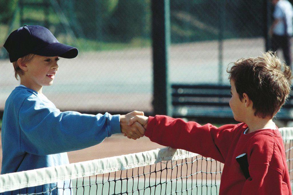 Girls shaking hands at net on tennis court : Stock Photo