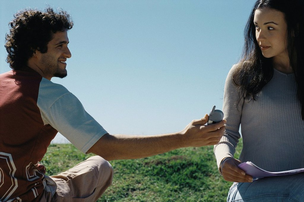Young man showing cell phone to woman : Stock Photo