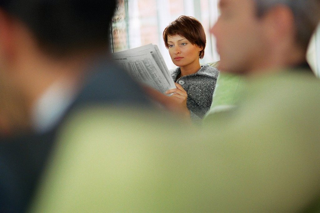 Businesswoman reading newspaper in waiting room : Stock Photo