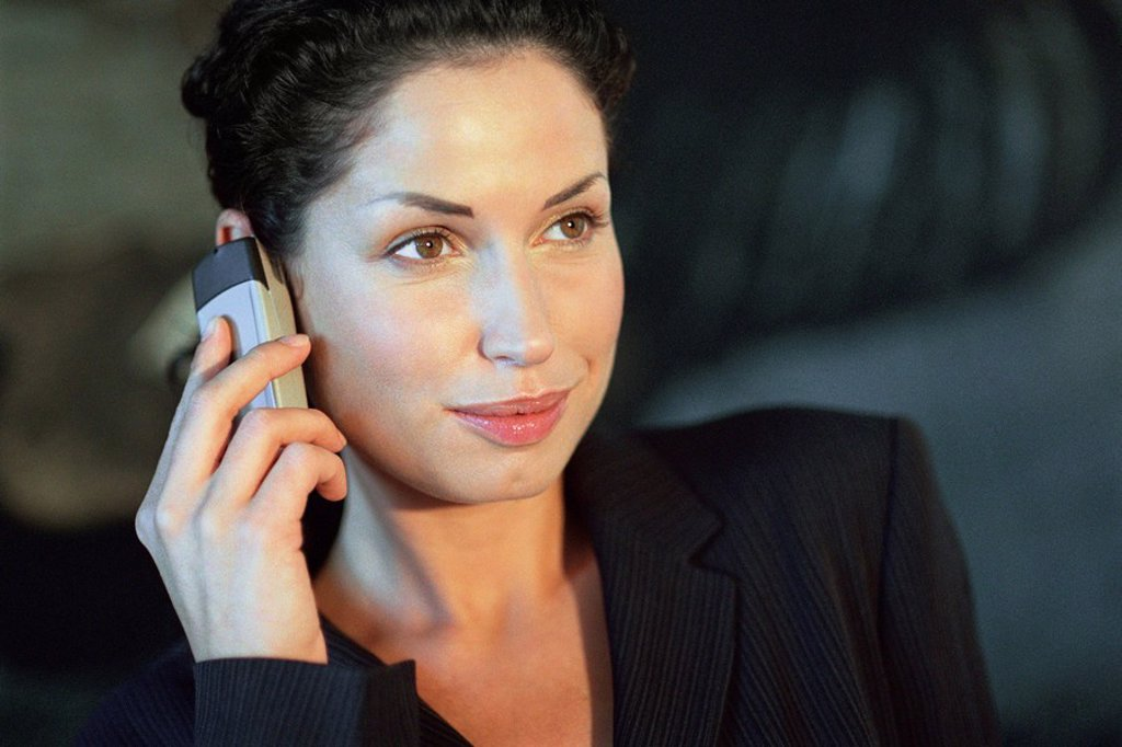 Young businesswoman using cell phone, smiling : Stock Photo