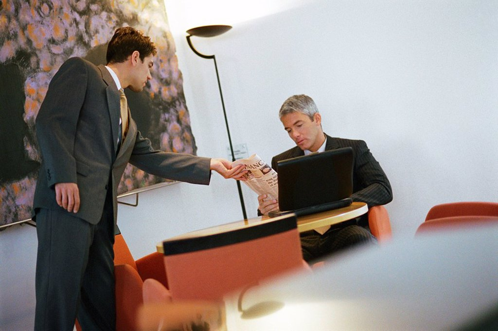 Businessman showing colleague financial section of newspaper : Stock Photo