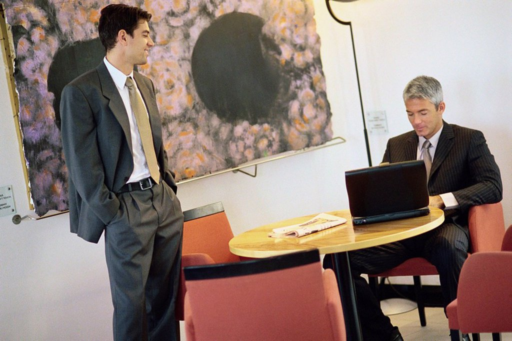 Businessmen chatting in break room, one using laptop computer : Stock Photo