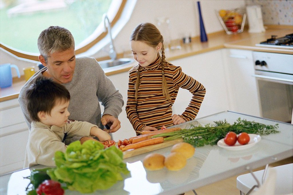 Father with children in kitchen, helping young son cut vegetables : Stock Photo