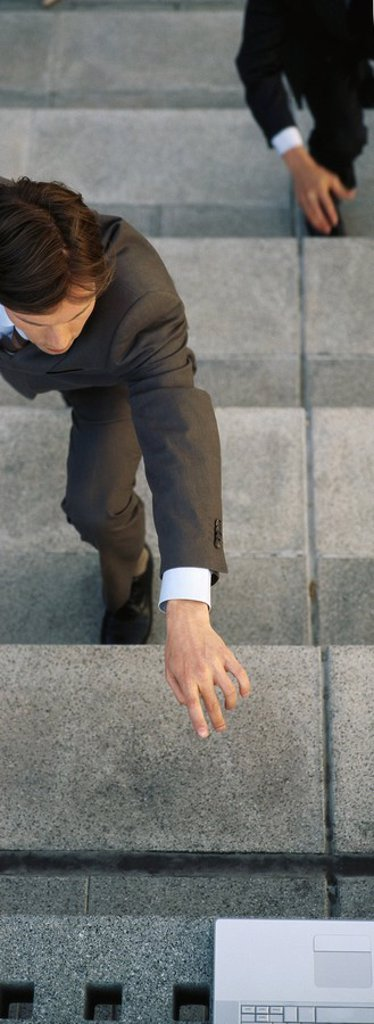 Stock Photo: 1569R-9056059 Businessmen crouching on steps reaching for laptop computer set at top of stairs