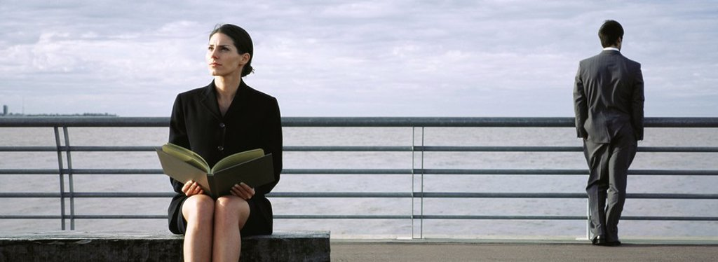 Stock Photo: 1569R-9056072 Businesswoman on bench at waterfront with open book on lap, man at railing looking at view in background