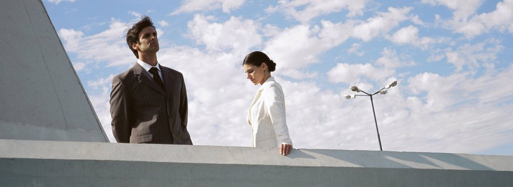 Stock Photo: 1569R-9056080 Businessman and businesswoman standing on rooftop, man looking at view, woman looking down