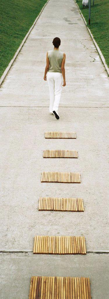 Woman walking along footpath, rear view : Stock Photo