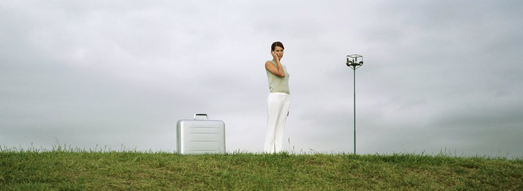 Woman standing in field using cell phone, briefcase on ground nearby : Stock Photo