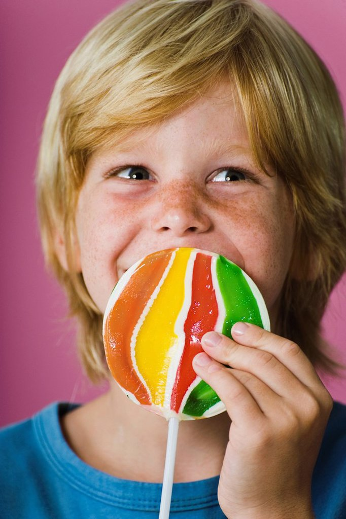 Boy holding large lollipop in front of face : Stock Photo