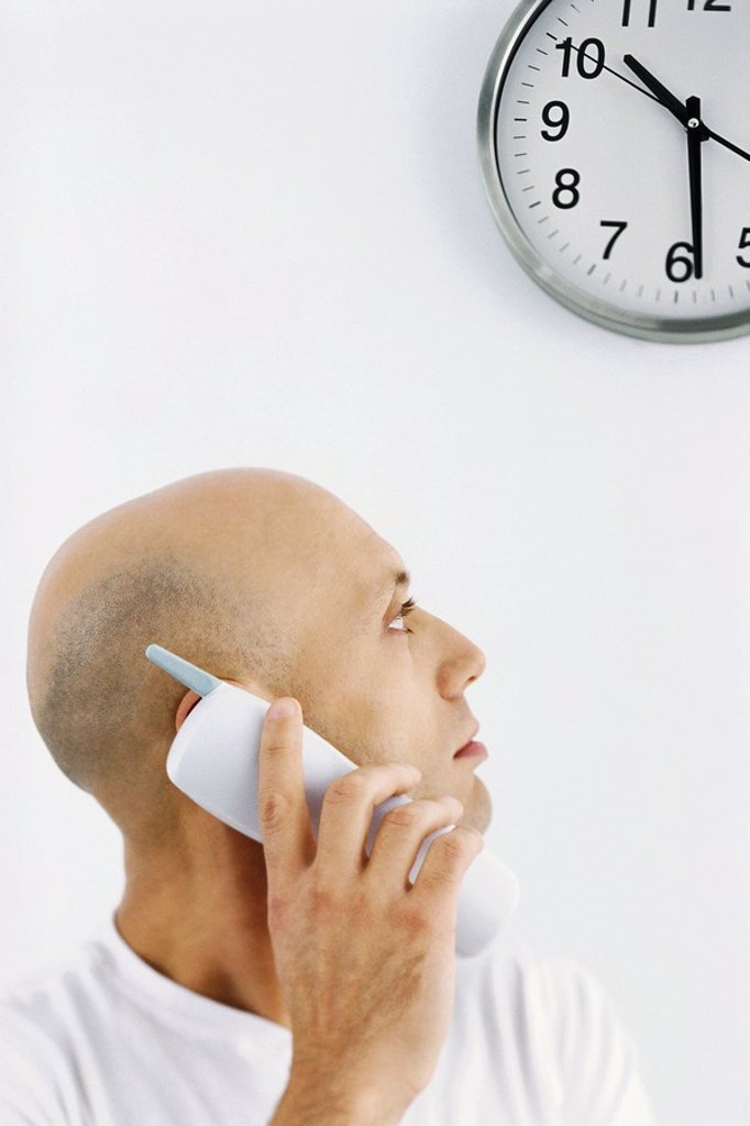 Man on phone call, looking over shoulder at clock : Stock Photo