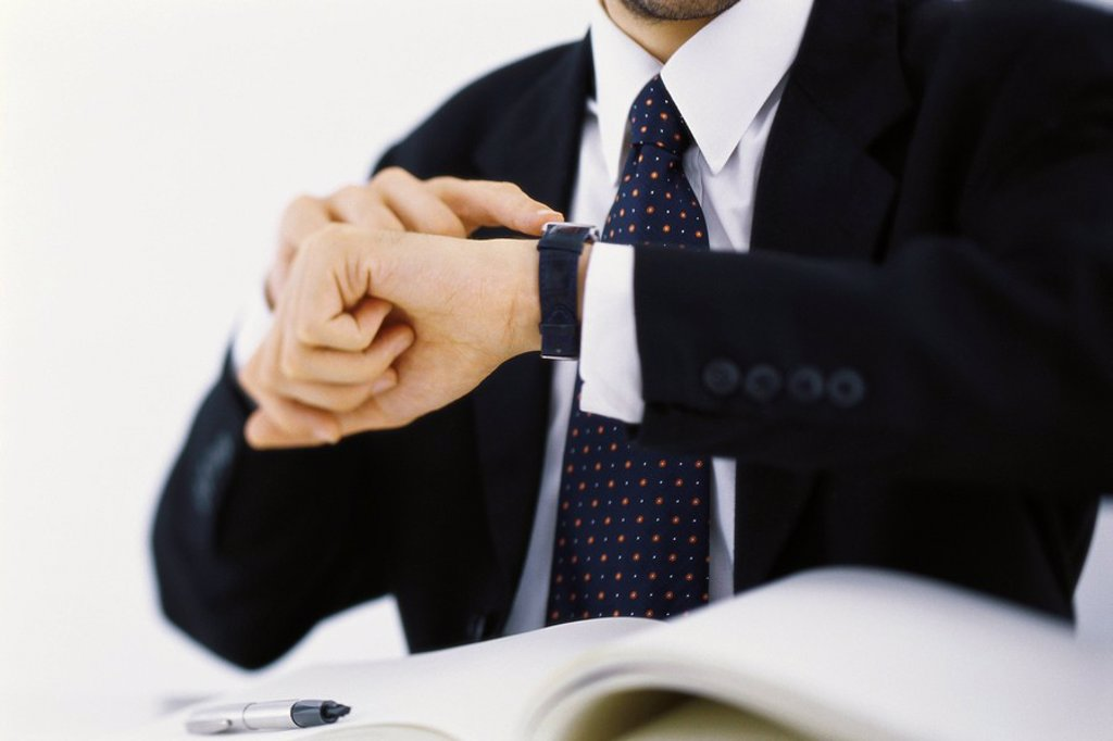 Businessman checking time on wristwatch, cropped : Stock Photo