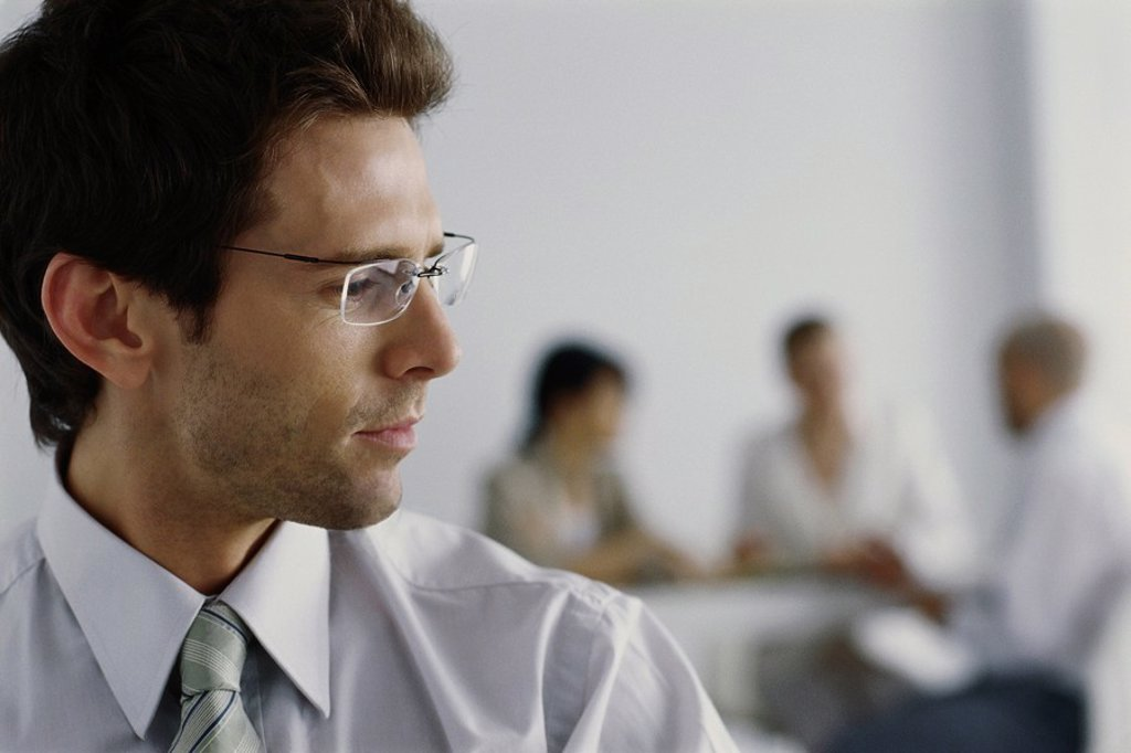 Young businessman in office, turning head to listen to colleagues in background : Stock Photo