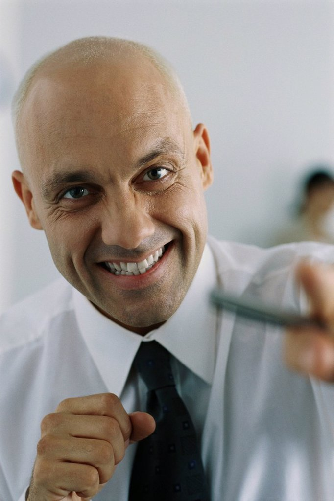 Businessman clenching fists, smiling at camera : Stock Photo