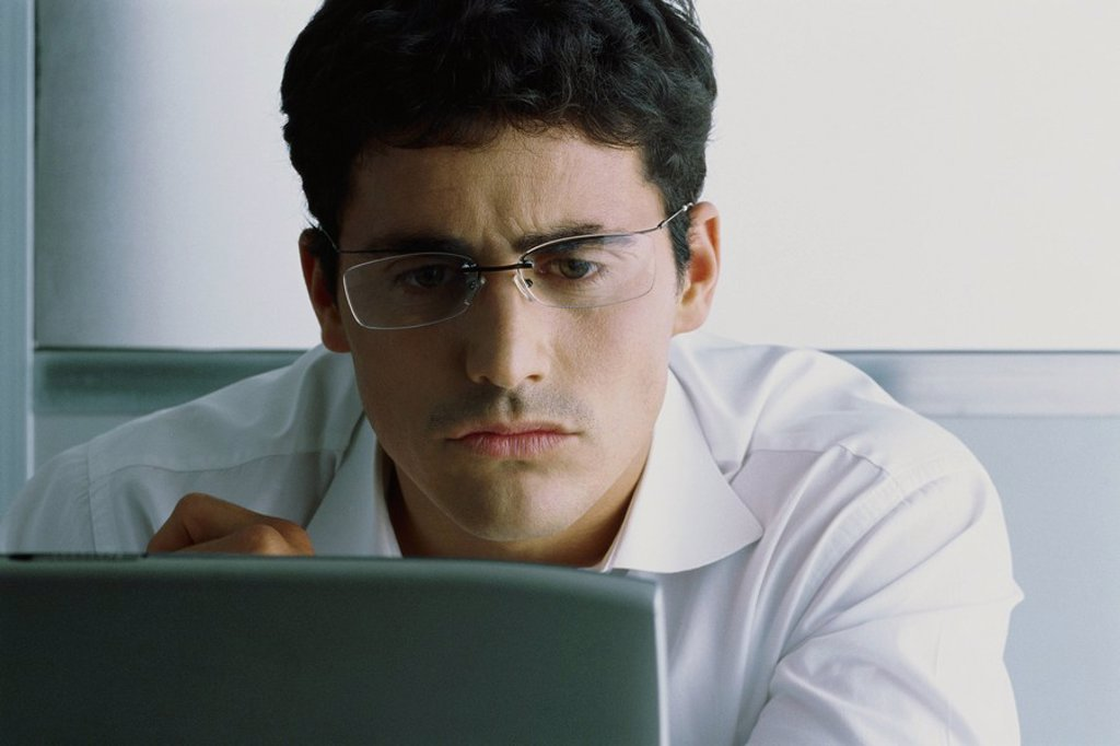 Man using computer, frowning : Stock Photo