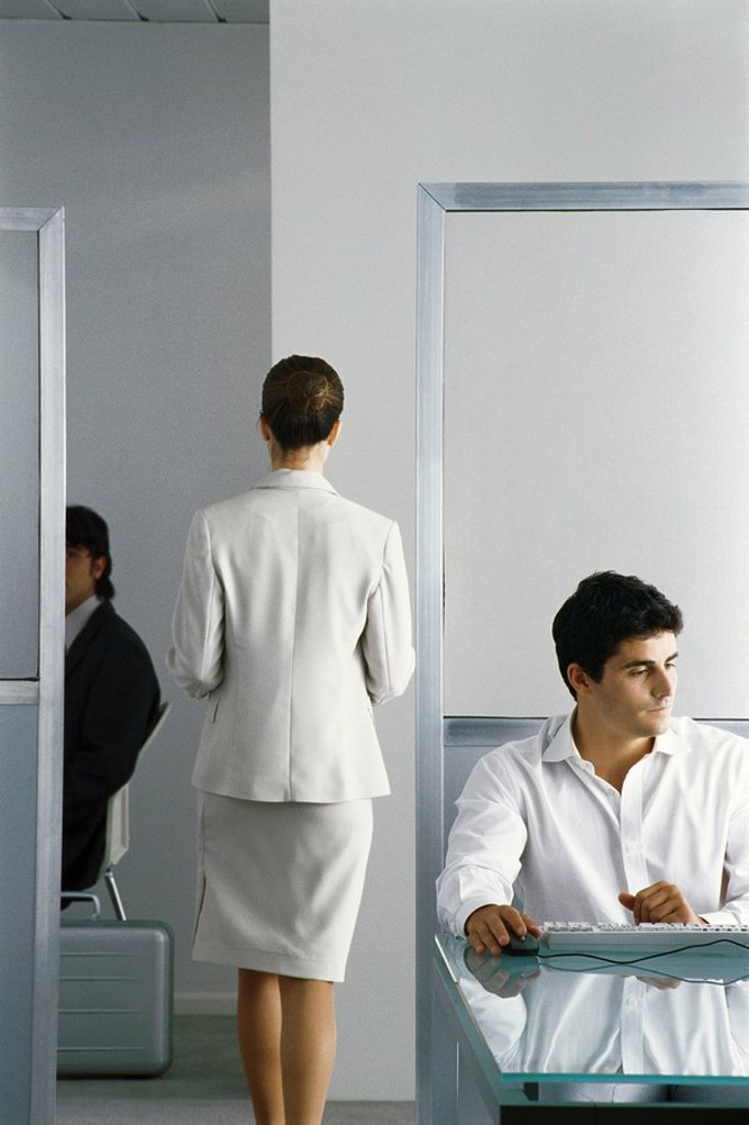 Female executive walking through office while colleagues work, rear view : Stock Photo