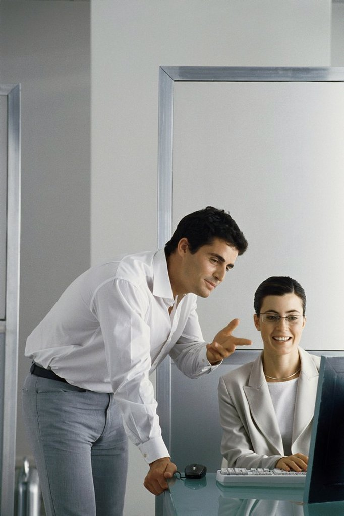 Office scene, man leaning on edge of desk speaking to female colleague, both looking at her computer screen : Stock Photo