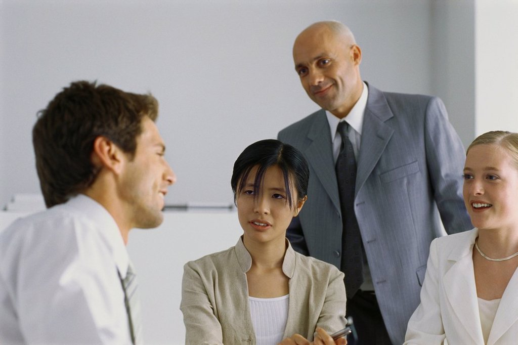 Four business associates having conversation, smiling : Stock Photo