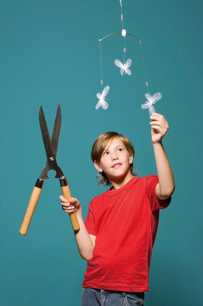 Boy with hedge clippers looking up at butterfly mobile : Stock Photo