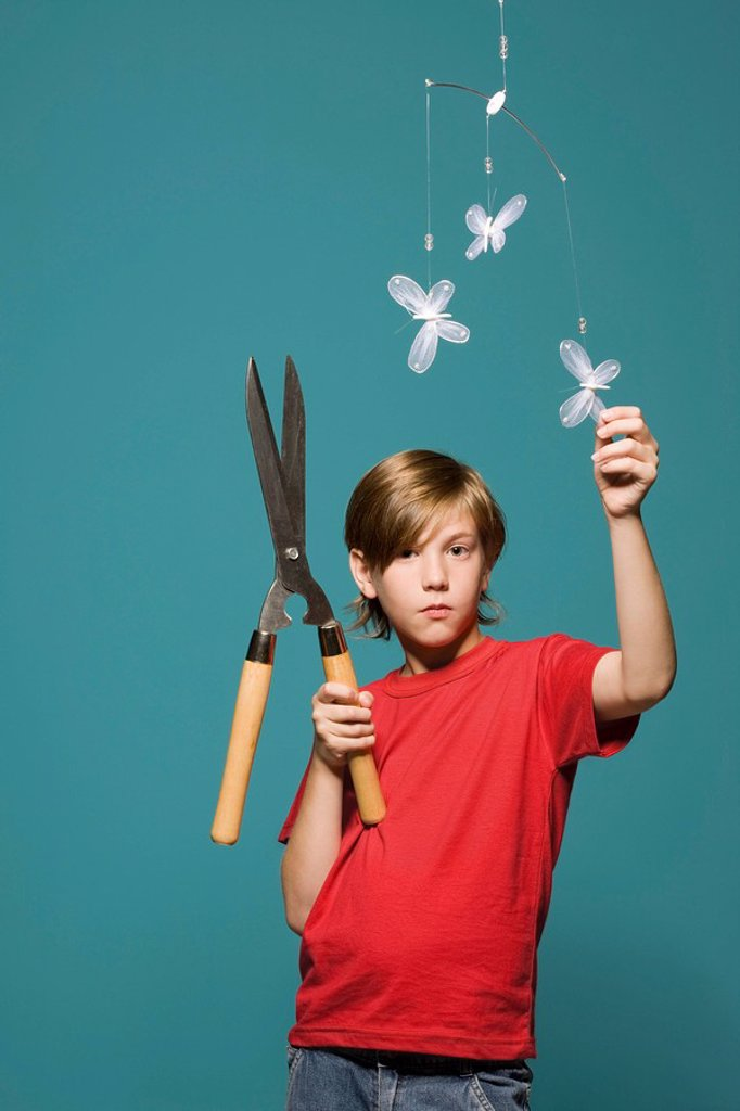 Boy standing below butterfly mobile, holding hedge clippers : Stock Photo
