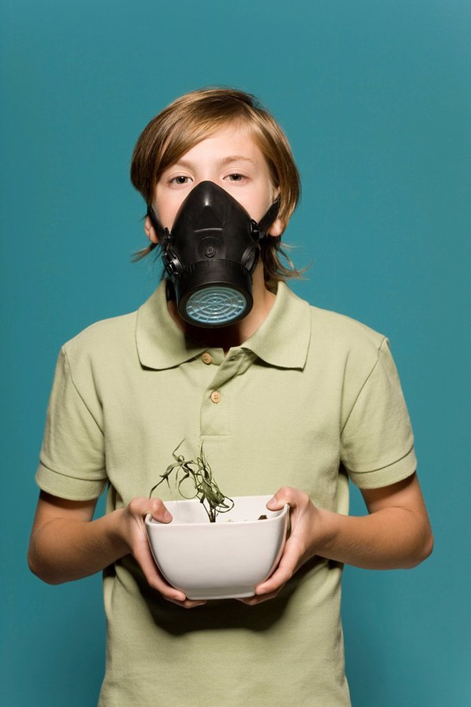Boy wearing gas mask, holding wilted potted plant : Stock Photo