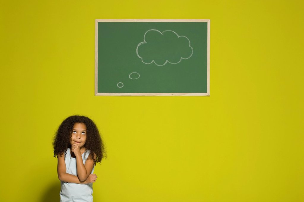 Stock Photo: 1569R-9056660 Little girl thinking, empty thought bubble on chalkboard overhead