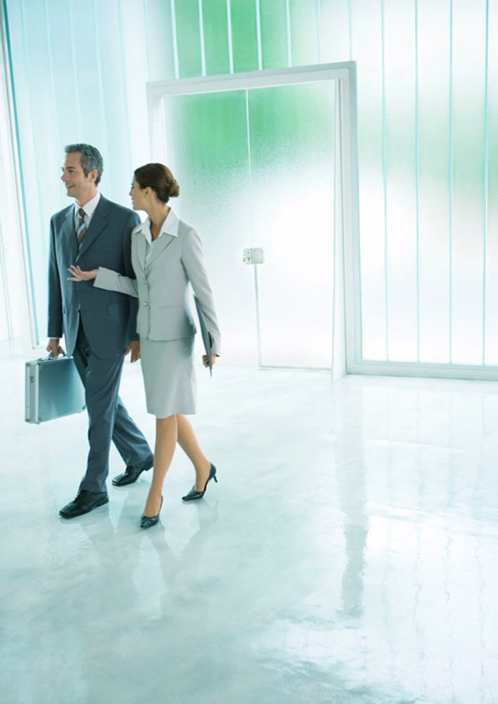 Female and male business associates walking through lobby : Stock Photo