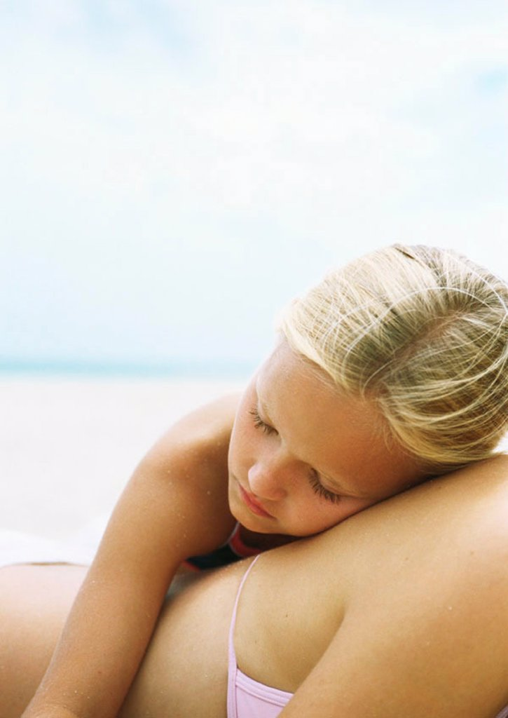 Little girl sleeping on mother´s back at the beach : Stock Photo
