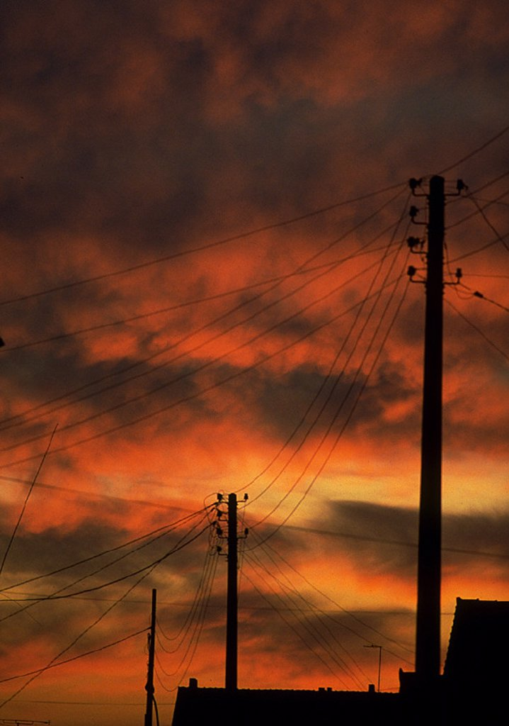 Electric poles silhouetted against red sky at sunset : Stock Photo