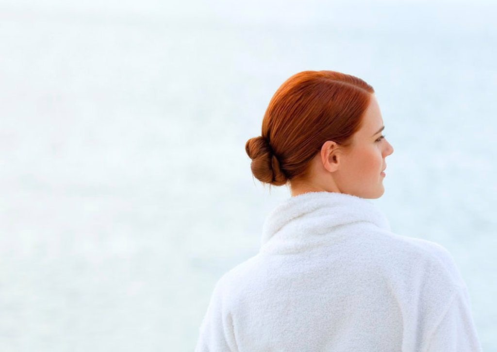 Woman wearing bathrobe, overlooking sea, rear view : Stock Photo