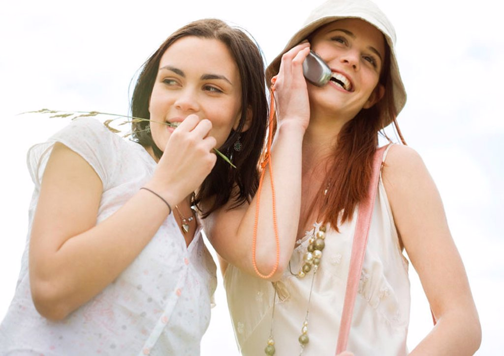 Two young woman outdoors, one using cell phone : Stock Photo