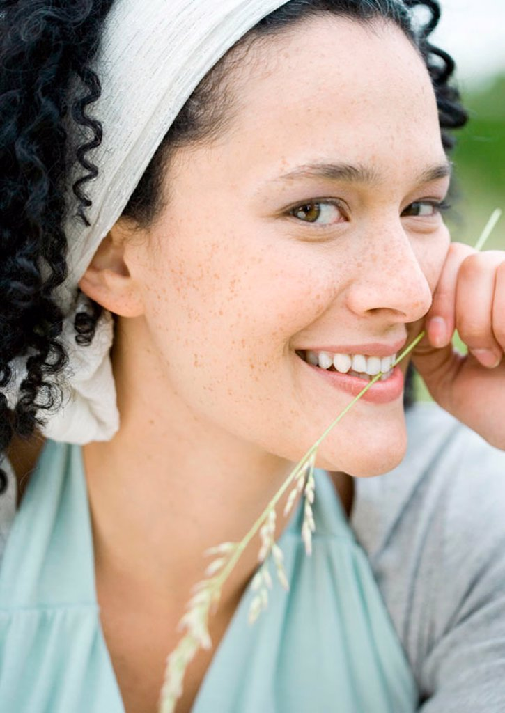 Young woman smiling, holding blade of grass : Stock Photo
