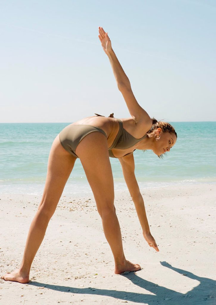 Young woman doing exercise on beach, rear view : Stock Photo