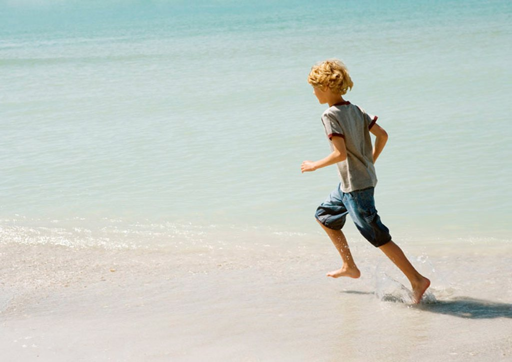 Boy running through surf at beach : Stock Photo
