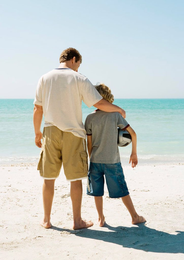 Stock Photo: 1569R-9058490 Father and son standing together on beach, boy holding ball under arm