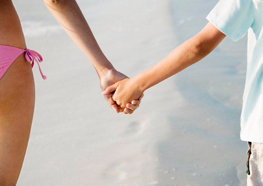 Stock Photo: 1569R-9058515 Child holding hands with older sister on beach, close-up
