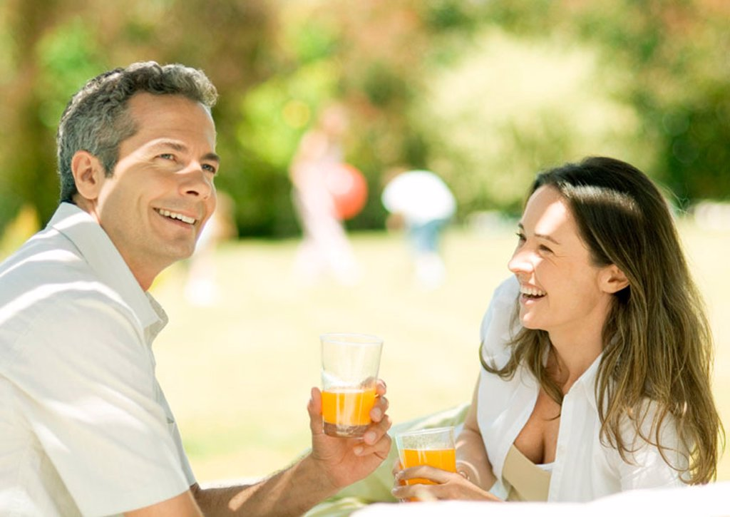 Couple holding glasses of juice outdoors : Stock Photo