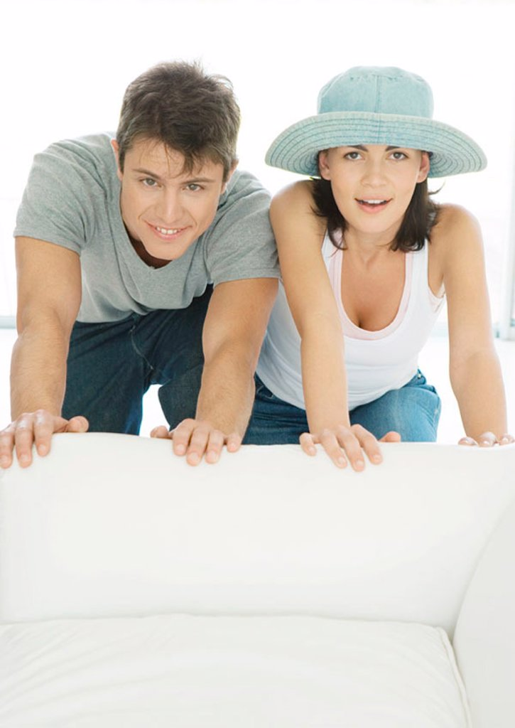 Stock Photo: 1569R-9058811 Couple moving armchair together