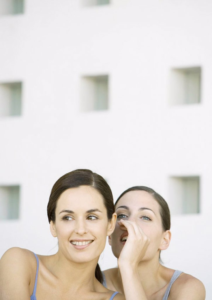 Young woman whispering to friend : Stock Photo
