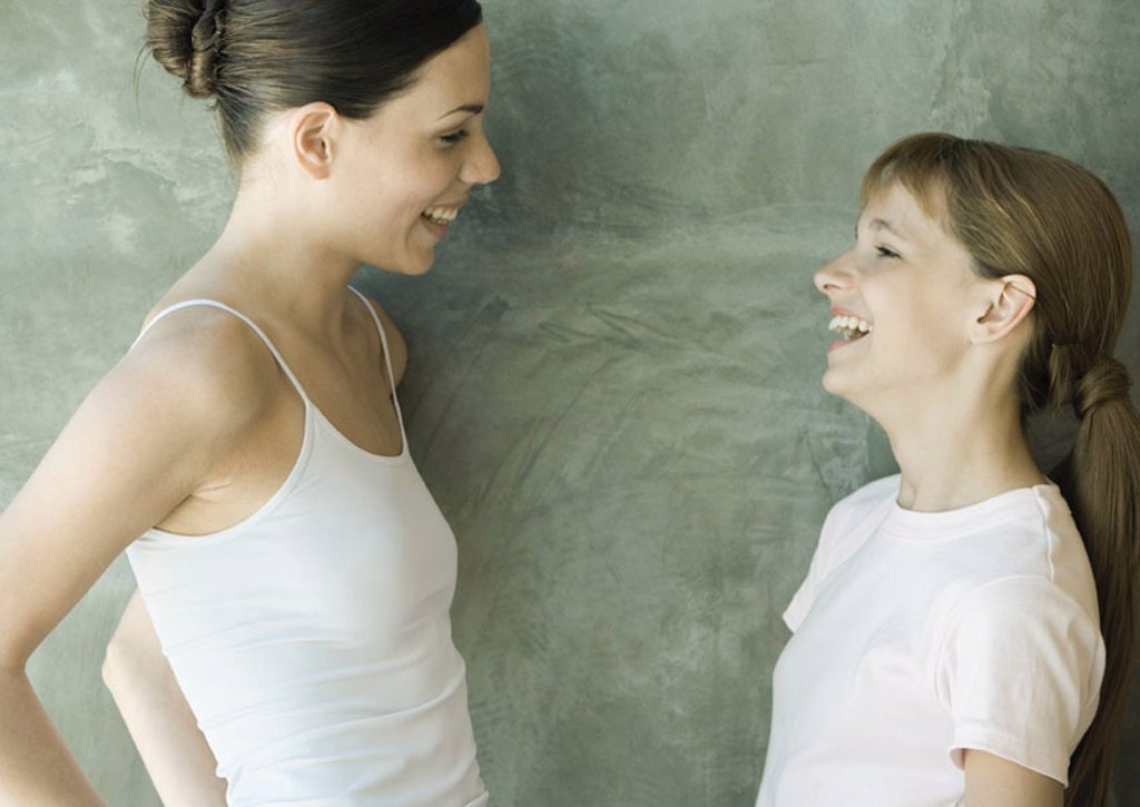 Two sisters standing, looking at each other and laughing, side view : Stock Photo