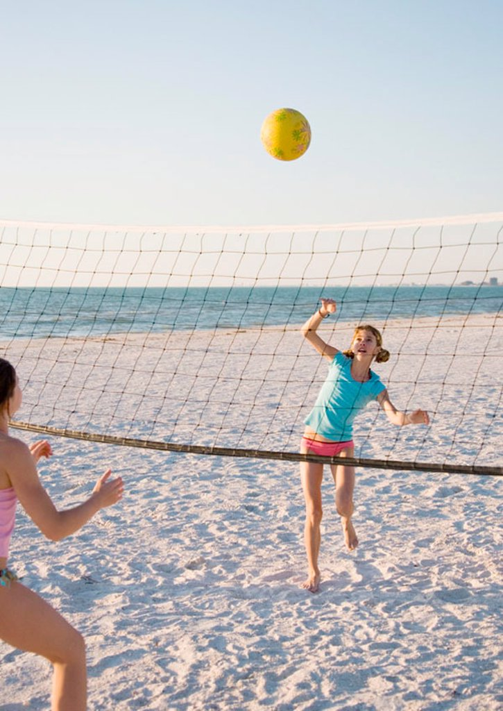 Two girls playing beach volleyball : Stock Photo