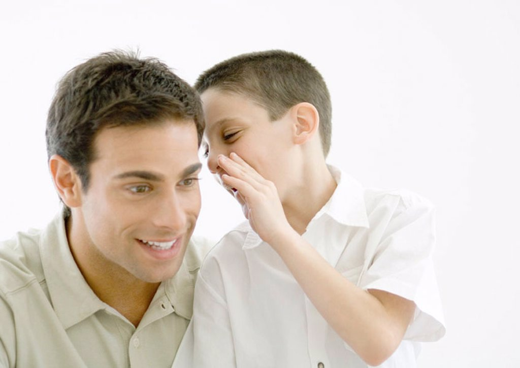 Stock Photo: 1569R-9058991 Boy whispering to father