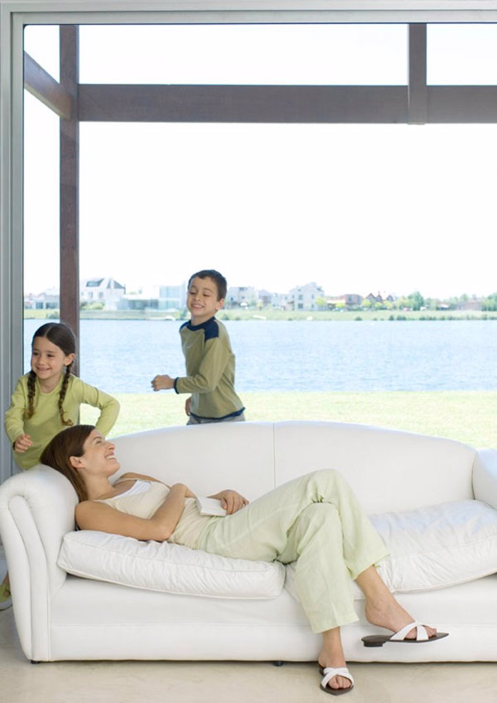 Mother reclining on sofa while children run around her : Stock Photo